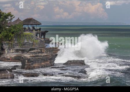 Waves crashing on Pura Tahah Lot sea temple on the Bali Sea, Indonesia - Stock Photo