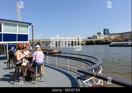 A group of people having drinks on a boat on the river Thames, London, England, United Kingdom - Stock Photo