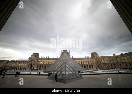The Louvre Museum parallel with the glass pyramid outside (Glass pyramid outside La Louvre, Paris) - Stock Photo