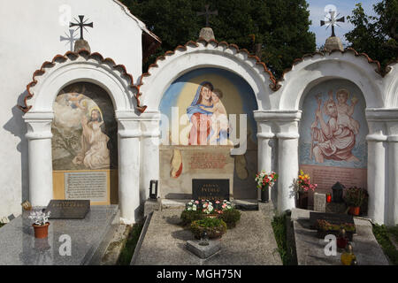 Funeral chapels with mural paintings at the village cemetery in Albrechtice nad Vltavou in South Bohemian Region, Czech Republic. Agony in the Garden, Madonna with Child and Saint Christopher are depicted in the chapels from left to right. Funeral chapels placed on the cemetery wall were decorated with murals in the 1840s by local painter František Mikule conducted with parish priest Vít Cíza, who also composed poems for each mural. The murals were repainted several times during the 19th and 20th centuries and completely restored by the team led by Jitka Musilová in 2010-2013. - Stock Photo