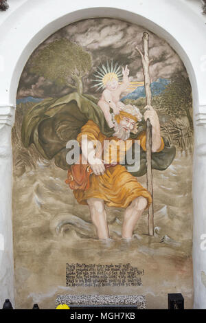 Saint Christopher carrying the Christ Child. Mural painting in the funeral chapel at the village cemetery in Albrechtice nad Vltavou in South Bohemian Region, Czech Republic. Funeral chapels placed on the cemetery wall were decorated with murals in the 1840s by local painter František Mikule conducted with parish priest Vít Cíza, who also composed poems for each mural. The murals were repainted several times during the 19th and 20th centuries and completely restored by the team led by Jitka Musilová in 2010-2013. - Stock Photo