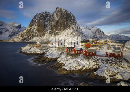 Fishermen cabins or rorbuer at the base of a snow-covered mountain. Hamnoy, Lofoten, Norway - Stock Photo