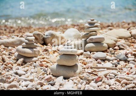 Stack of stones on the sea summer beach.The pile of the pebbles on the stony coast.Stones pyramid on pebble beach symbolizing stability, zen, harmony, balance. Tropical sea beach. Vacation concept - Stock Photo