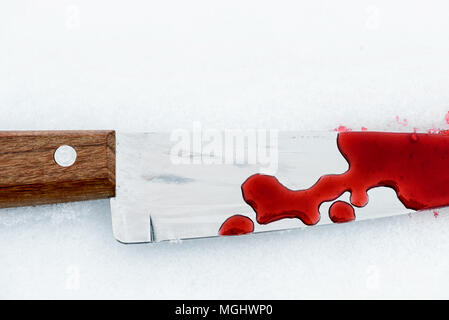 Sharp metal kitchen knife edge used as a violent murder weapon with blood drops on a white snow background. Blade covered in violence with copy space  - Stock Photo