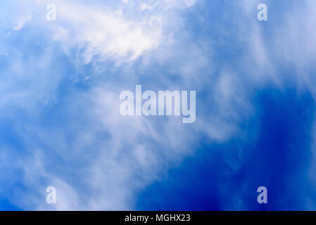 Wispy white clouds and turbulent sky taken during a winter's day with crisp blue areas of natural skyline - Stock Photo