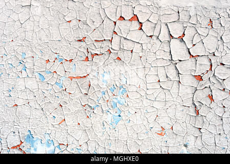 Old flaking blue paint with an orange vibrant undercoat showing up through cracked broken plaster with a copyspace area for DIY reconstruction and bui - Stock Photo