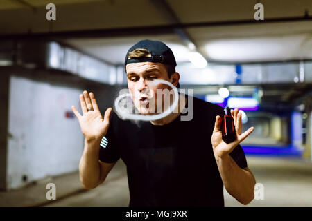 Man in cap smoke an electronic cigarette and releases clouds of vapor performing various kind of vaping tricks - Stock Photo