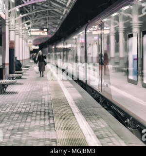 Railway subway station, at night, at dusk, passenger train stopped. Unrecognizable girl goes on the platform. Passenger transportation, style of life. - Stock Photo