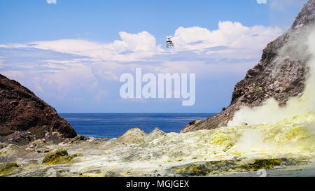 A helicopter coming in to land in the crater. White Island / Whakaarian volcano, New Zealand - Stock Photo