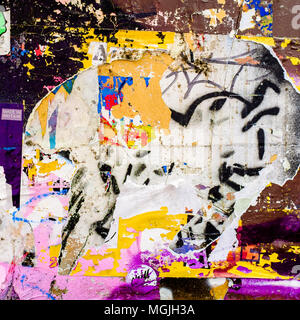 Urban Collage  Décollage. Remnants of torn posters on wall, London, UK - Stock Photo
