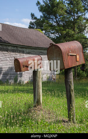 Rusted out mailbox along a country road; gas pump a memory of days gone by. Rural decay tells a story amidst the rust, neglect, and overgrowth. - Stock Photo