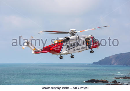 A Sikorsky S92 search and rescue helicopter of the Maritime and Coastguard Agency flies on practice manoeuvres with the RNLI at Bude, North Cornwall - Stock Photo
