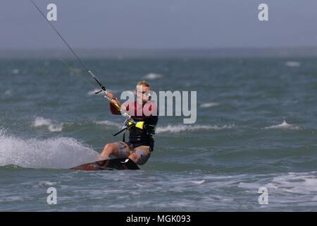 Kitesurfing with lots of spray in Punta Chame lagoon, Panama - Stock Photo