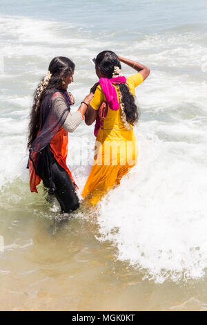 MASI MAGAM FESTIVAL, PUDUCHERY, PONDICHERY, TAMIL NADU, INDIA - March 1, 2018. Unidentified Indian pilgrims women with colored Sari bathing in the sea - Stock Photo