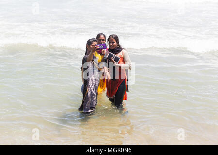MASI MAGAM FESTIVAL, PUDUCHERY, PONDICHERY, TAMIL NADU, INDIA - March 1, 2018. Unidentified Indian pilgrims women with colored Sari bathing taking sel - Stock Photo
