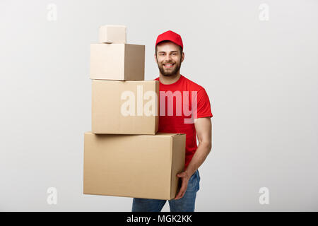 Delivery Concept: Handsome delivery man hold pile cardboard boxes on grey background. - Stock Photo