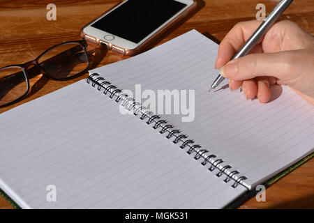 Woman with pen in hand, poised to write in a spiral bound notebook - Stock Photo