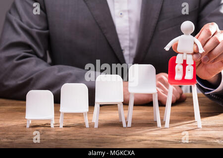 Close-up Of A Businessperson's Hand Placing Human Figure On Red Chair Over Wooden Desk - Stock Photo