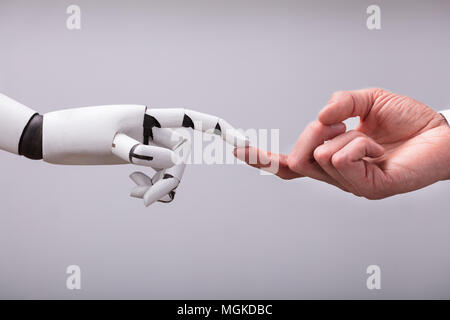 Robot Touching Human Finger Against Gray Background - Stock Photo