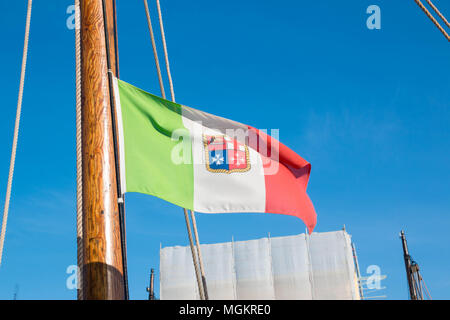The italian army flag on a wooden boat flagpole on a sunny day in cesenatico. - Stock Photo