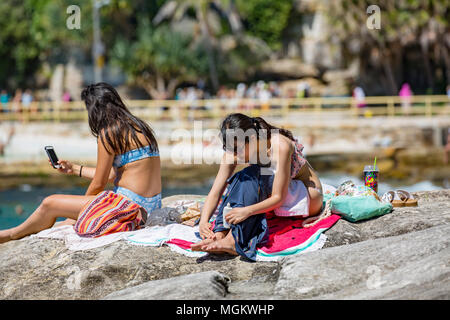 Young black hair asian girls sunbathe on the rocks at Fairy Bower in Manly beach,Sydney,Australia - Stock Photo