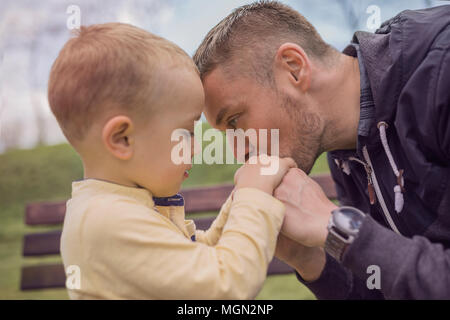 Closeup portrait of a happy father and son playing on playground and having fun. Young father playing with his baby outside in park. Dad and son. - Stock Photo