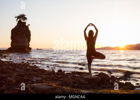 Young Woman practicing yoga on a rocky shore during a vibrant sunset. Taken in Stanley Park, Vancouver, British Columbia, Canada. - Stock Photo