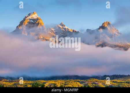 Sunrise with morning fog and mist on the Grand Tetons Mountain Range in the Grand Tetons National Park in Wyoming. - Stock Photo