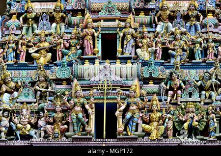 Front view of a group of colorful stone statues depicting Indian Hindu Gods and Deities on the exterior of an old temple in Little India, Singapore - Stock Photo