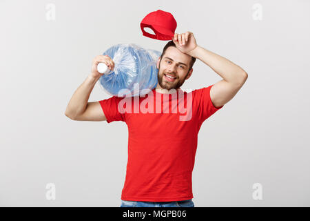 Delivery Concept: Portrait of smiling bottled water delivery courier in red t-shirt and cap carrying tank of fresh drink isolated over grey background - Stock Photo