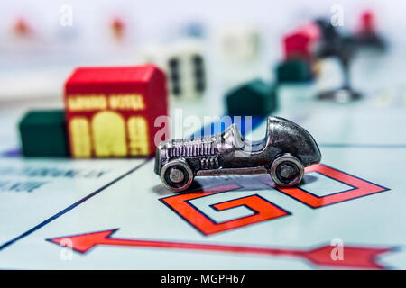 Monopoly Board Game close up with the car passing the GO. - Stock Photo
