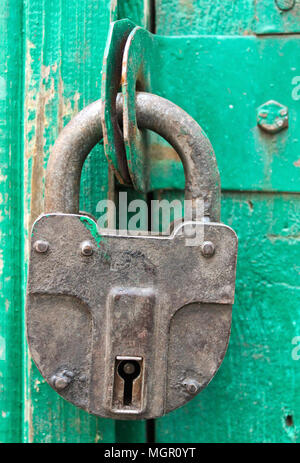 Padlock hanging on a wooden barn door - Stock Photo