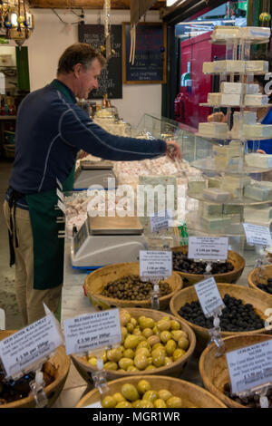 a stall holder or market trader selling fresh olives and continental speciality cheeses at a stall on borough market in london. high quality foods. - Stock Photo