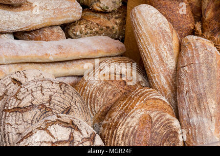 A selection of artisan bakery bred rolls and loaves on display at a bakers stall on borough market in london. Freshly baked artisan bread at bakery. - Stock Photo