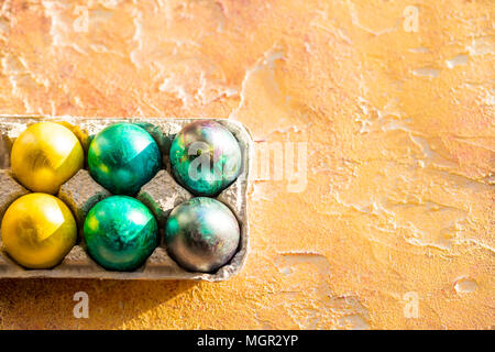 Easter eggs in a panels paper on yellow table. Easter egg painting with colorful during the Easter.pack of eggs corner on yellow orange background. Copy space - Stock Photo