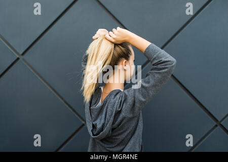 Epic back view of strong fit female athlete getting ready for workout towards the sun. Strong fitness woman tying ponytail. - Stock Photo