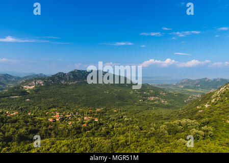 Montenegro landscape with balkan mountain village and rocks by cloudy day. Montenegrin wild nature scenery panoramic view with small town in the mount - Stock Photo