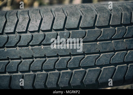 Old worn tire with a worn tread - Stock Photo