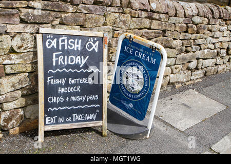 fish n' chip shop sign or a-board on pavement outside cafe - Stock Photo
