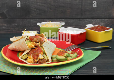 Egg burritos wtih eggs, chorizo, avocado, cheese and salsa.  Rustic wooden table and wall, condiments on the side. - Stock Photo