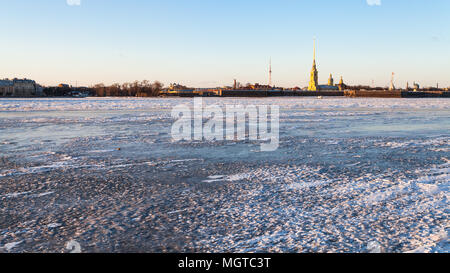panoramic view of frozen Neva river and Peter and Paul Fortress in Saint Petersburg city in March evening - Stock Photo