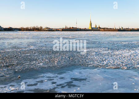 view of frozen Neva river and Peter and Paul Fortress in Saint Petersburg city in March evening - Stock Photo