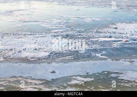frozen water of Neva river near Dvortsovaya Embankment in Saint Petersburg city in March evening - Stock Photo