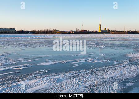 view of ice covered Neva river and Peter and Paul Fortress in Saint Petersburg city in March evening - Stock Photo
