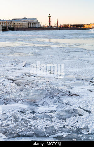 ice-bound Neva river and Spit of Vasilyevsky Island with Rostral Column and Old Stock Exchange building in Saint Petersburg city in March evening - Stock Photo