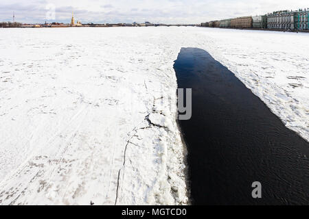 view of frozen Neva river with polynya near Dvortsovaya embankment in Saint Petersburg city in March - Stock Photo