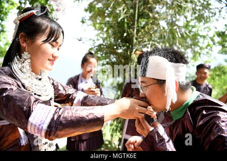 Rongjiang, China's Guizhou Province. 29th Apr, 2018. A woman of Miao ethnic group toasts a guest at Sanpan Village of Rongjiang County in the Miao and Dong Autonomous Prefecture of Qiandongnan, southwest China's Guizhou Province, April 29, 2018. People in China spend their Labor Day holiday in various ways. Credit: Wang Bingzhen/Xinhua/Alamy Live News - Stock Photo