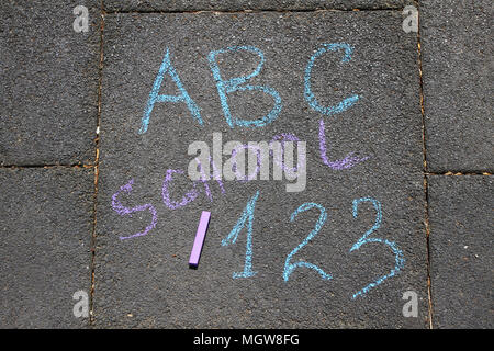 School, ABC letters and 123 sigh written with colored chalks on a pavement. Drawing Back to school on an asphalt. and vacation concept. Education conc - Stock Photo