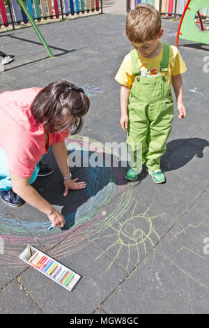 Mom and cute boy draw with colorful chalks on asphalt. Summer activity and creative games for small kids. Quality family time. Happy mother's day. Mot - Stock Photo