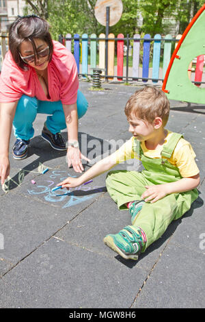 Mom and cute boy draw alphabet with colorful chalks on asphalt. Summer activity and creative games for small kids. Family time. Happy mother's day. - Stock Photo
